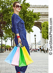 elegant woman in sunglasses with shopping bags on Champ...