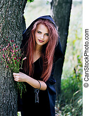 witch gathers herbs - young beautiful witch gathers herbs...
