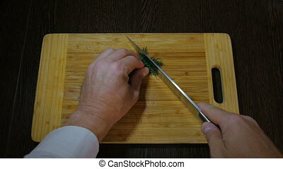 Chef cuts dill on a cutting board. To add a vegetarian dish.