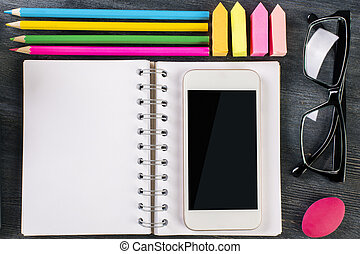 Smartphone, notepad and supplies - Top view and close up of...
