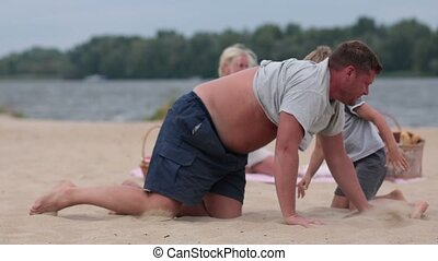 Father giving his son piggyback ride at the beach