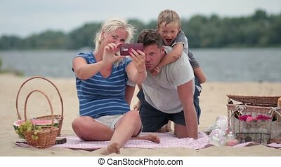 Beautiful family at beach making selfie with phone