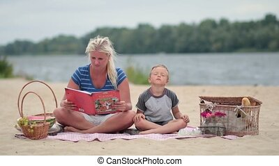 Mother reading book to cute son at the beach
