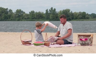 Happy family playing pillows fight on beach