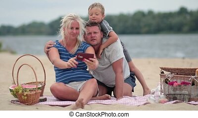 Smiling family making a self portrait with phone - Happy...