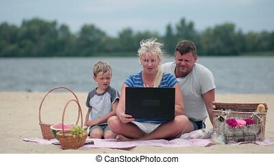 Family using laptop to talk to grandmom - Family on vacation...