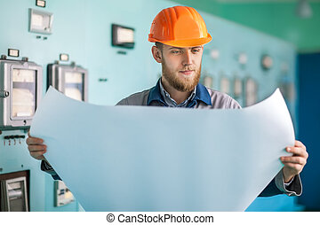 Portrait of young engineer working with blueprint at control...