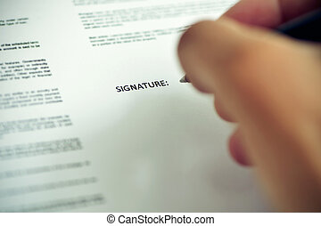 man signing a document - closeup of a young caucasian man...