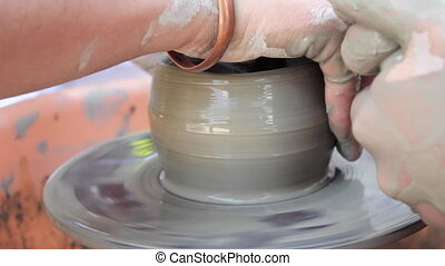 Potter teaches his craft to the children. Pottery class workshop. Clay shaping on potter's wheel and firing