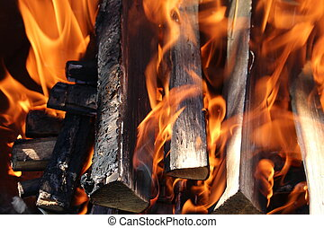 Fire on dark wood - Charred wood and bright flames on dark...