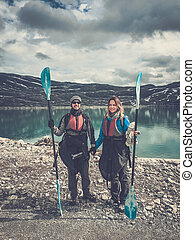 Happy couple of kayakers standing with paddles near...