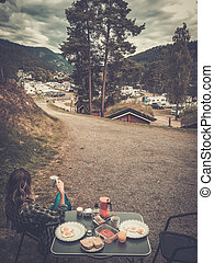 Woman hiker having breakfast in the open air at the campsite...