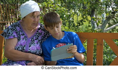 Grandson showing grandmother how to use tablet. Sitting on a...