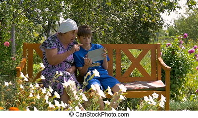 Grandson showing grandmother how to use tablet