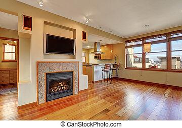 Open floor plan. View of fireplace in the living room with hardwood floor.