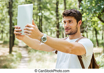 Happy man with backpack taking selfie using tablet in forest