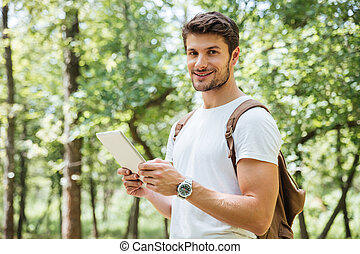 Cheerful young man with backpack using tablet in forest