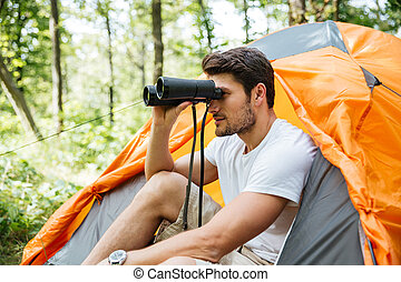Man tourist with binoculars sitting near touristic tent in forest