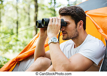 Man tourist sitting and looking at binoculars in forest