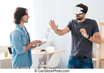 Pleasant young colleagues testing virtual reality device -...