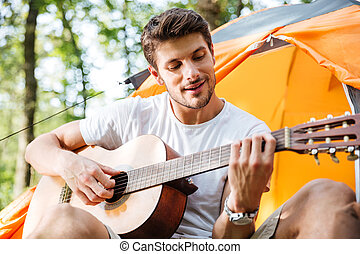 Happy young man tourist sitting and playing guitar in forest...