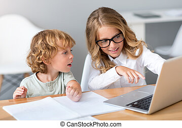 Girl pointing at screen of laptop
