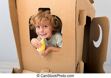 Cute boy sitting in carton rocket - Departure time. Cute...