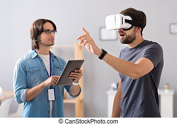 Pleasant colleagues testing virtual reality glasses -...