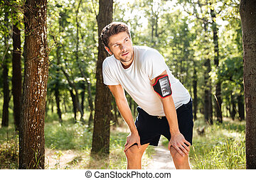Exhausted young man athlete standing after running in forest...