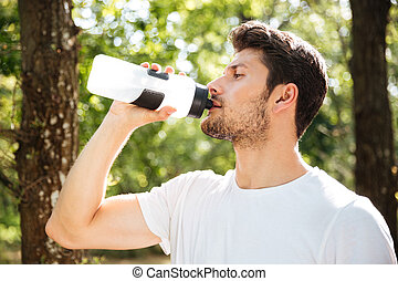 Handsome young man athlete drinking water in forest -...