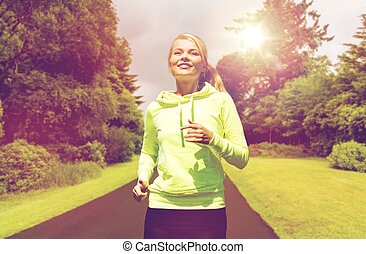 happy smiling young woman jogging outdoors - fitness, sport,...