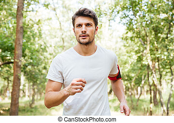 Man athlete with handband running outdoors in the morning -...