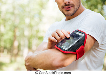 Closeup of young man athlete using mobile phone in handband...