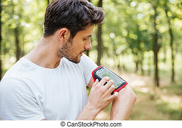 Attractive young man athlete using mobile phone in handband...