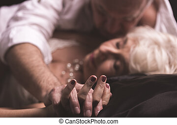 Love kissing your body - Elder couple lying together on a...