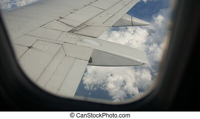 Ground and clouds under wing of an airplane during flight