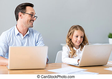 Cheerful man and girl working on laptops - Involved in work...