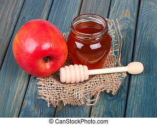 Honey and apple on rustic wooden table