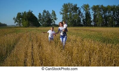 mother with children running in wheat field slowmotion