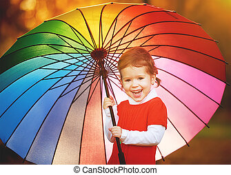 happy little child girl with multicolored rainbow umbrella in park