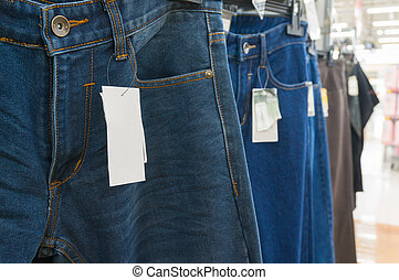 Blank White Tag over the Blue Jeans on Hanger Shelf in...