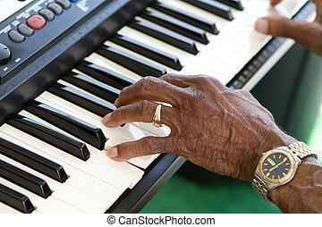 Keyboard Player - Hands of an elderly african american man...