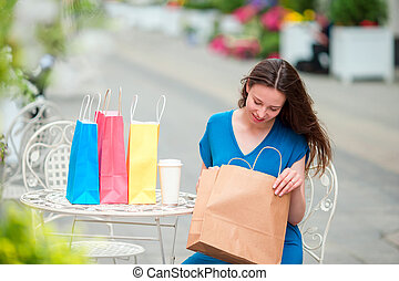 Fashion happy girl with bags after shopping drinking coffee...