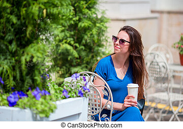 Fashion happy girl drinking coffee in openair cafe....
