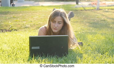 Woman on laptop outside on grass - Woman on laptop outside...