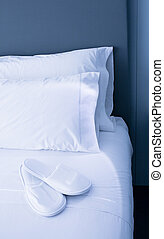 Pillows and slippers on bed - Bed sheets and white pillows...