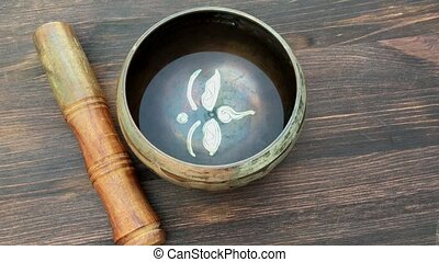 Tibetan singing bowl - Singing bowl with water and a wooden...
