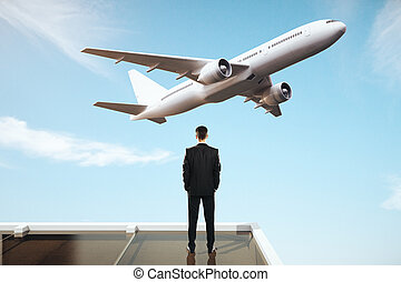 Businessman looking at plane