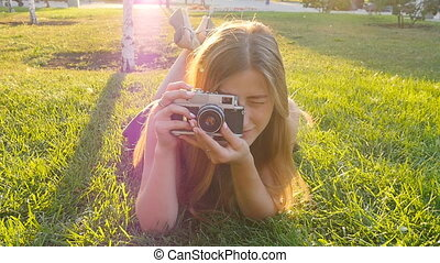 woman the photographer with old camera lays on a grass