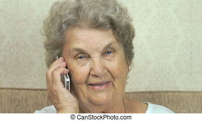 Old woman talking on the mobile phone indoors